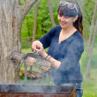 Woman cooking over a BBQ reacting in horror — Stock Photo #45275771