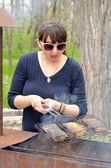 Woman cooking over a BBQ reacting in horror — Stock Photo