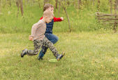 Two small boys running across a field — Stock Photo