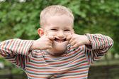 Schattige jonge jongen trekken een grappige expressie — Stockfoto