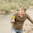 Man looking at fresh yellow wildflowers — Stock Photo #46978717