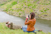 Young woman photographing a man on a cliff top — Stock Photo