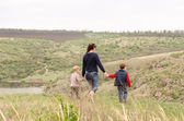 Mother walking with two boys in the countryside — Stock Photo