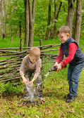 Two young boys extinguishing a small fire — Stock Photo