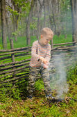 Little boy putting out a camp fire — Stock Photo