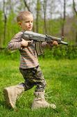 Boy carrying a machine gun saluting — Stock Photo