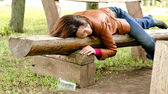 Drunk woman sleeping it off on a wooden bench — Stock Photo