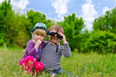 Two young children playing with binoculars — Stock Photo