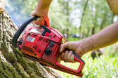 Man using a two-stroke petrol chainsaw — Stock Photo