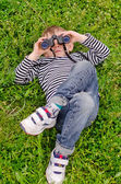 Young boy lying on his back with binoculars — Stock Photo
