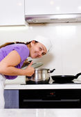 Smiling cook bending over a pot on the stove — Stock Photo
