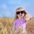 Adorable little blond girl in huge sunglasses — Stock Photo #48738675