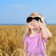 Cute little blond girl playing in a wheat field — Stock Photo #48738681