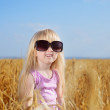 Cute little blond girl playing in a wheat field — Stock Photo #48738693