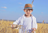 Trendy young boy playing in a field with a plane — Stock Photo