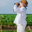 Little boy standing in farmland using binoculars — Stock Photo