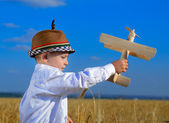 Cute young boy playing with a wooden biplane — Stock Photo