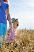 Little girl walking in a wheat field with mother — Stock Photo