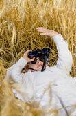 Schattige jongen liggen in een veld met rijpe tarwe — Stockfoto