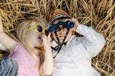 Jongen en meisje speelt in gras met verrekijkers — Stockfoto