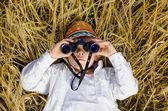 Roztomilý chlapec vleže v oblasti zralé pšenice — Stock fotografie