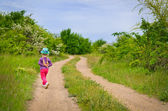 Small girl in a colorful outfit on a country track — Stock Photo