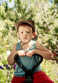 Thoughtful young boy sitting in a country garden — Stock Photo