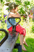 Little boy sulking as he sits on a seesaw — Stock Photo