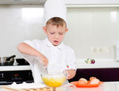 Young boy baking whipping eggs — Stock Photo