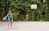 Young girl dribbling a basketball — Stock Photo