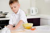 Cute little boy learning to bake cakes — Foto de Stock