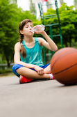 Tired young girl drinking water — Stock Photo