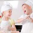Happy little boy and girl cooking in the kitchen — Stock Photo #51009147