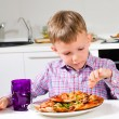 Little boy eating a big plate of pizza — Stock Photo #51009215