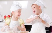 Happy little boy and girl cooking in the kitchen — Stock Photo
