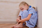 Sad young girl sitting in corner — Stock Photo