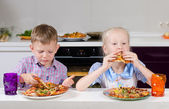 Happy little boy and girl eating Italian pizza — Stock Photo