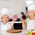 Two smiling children holding up fresh vegetables — Stock Photo