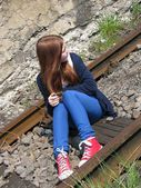 Young girl sitting on rails — Stock Photo