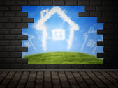 Cloud houses in hole in brick wall — Stock Photo