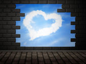 Heart of clouds in hole in brick wall — Stock Photo
