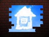 Casa de nuvens no buraco na parede de tijolo — Fotografia Stock