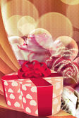 Holiday background with gift box and roses — Stock Photo