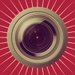 Camera lens on red background — Photo
