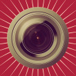 Camera lens on red background — Stockfoto