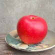 Red apple on plate — Stock Photo