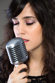 Attractive young woman with a retro microphone — Stock Photo
