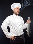 Young handsome chef with seabass fish — Stock Photo
