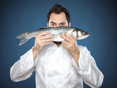 Young handsome chef with sea bass — Stock Photo