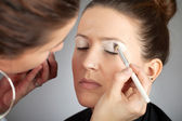 Make-up artist applying white eye shade — Stock Photo